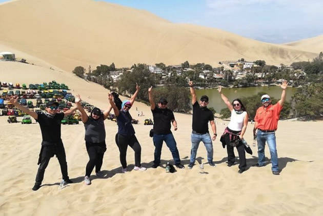 Day tours in Lima: Triumphant sand surfing tourists.