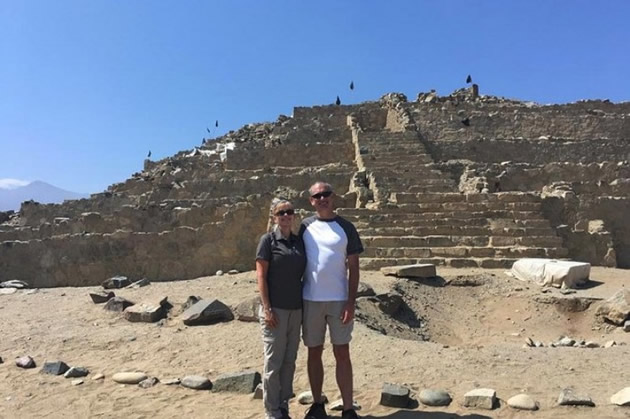 Day tours in Lima: Couple poses beside ancient Peruvian pyramid.