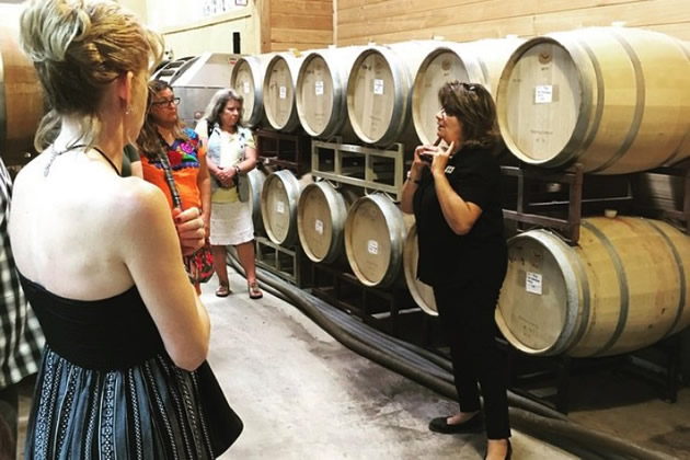 A host leads a group on a wine tour in the Hill country of Texas outside of San Antonio.