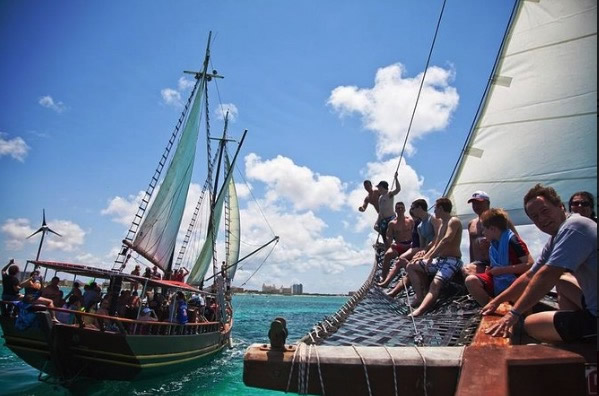Tourists wait their turn to rope swing off a pirate ship.