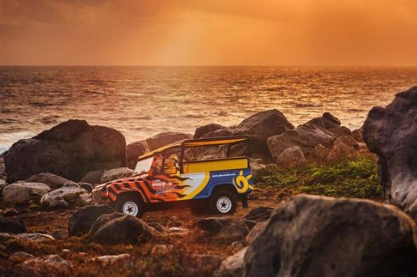 Flame-painted Jeep along a rocky Aruba coast.