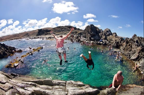 Tourists jump into the clear turquoise water of an Aruban volcanic pool.