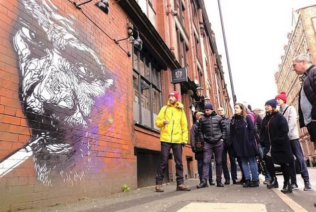 Yellow-clad guide points out a musical wall mural on a Manchester street.
