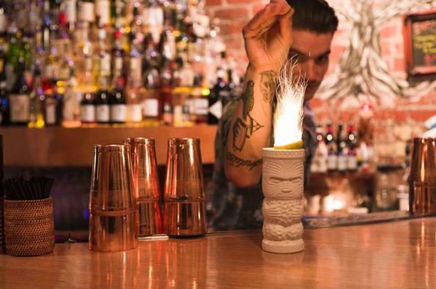 Tattooed bartender sets a cocktail aflame.