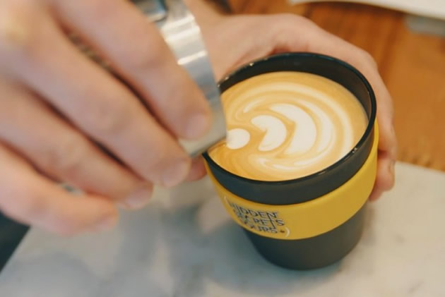 Barrista decorates a foaming latte with a leaf pattern.