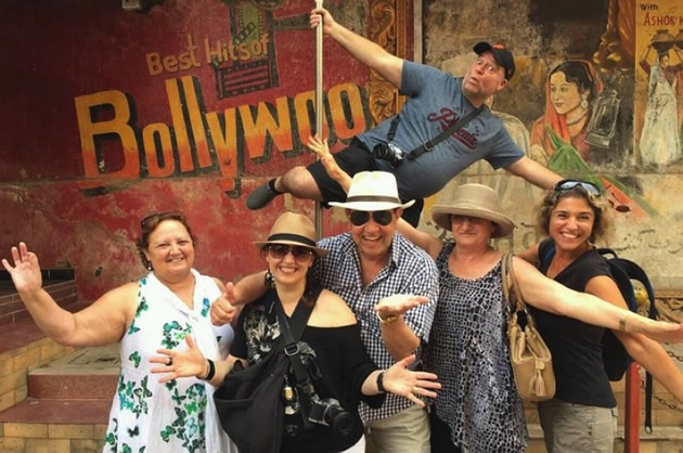 Tourists ham it up by a Bollywood sign.