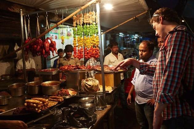 Tourists experience a colorful Mumbai food stall.