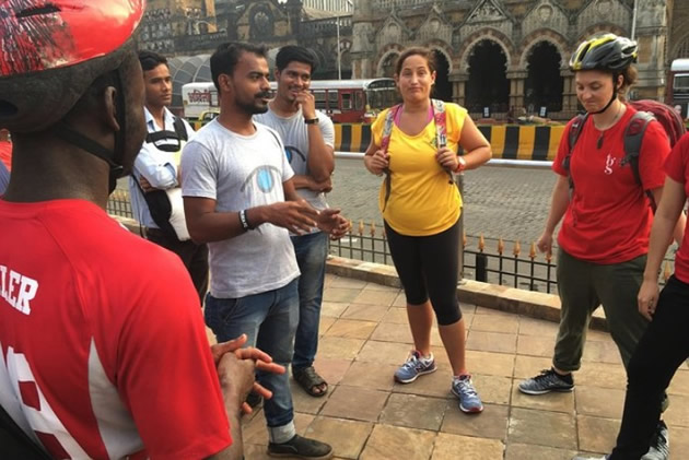 Helmeted tourists get instructions for their bike ride in Mumbai.