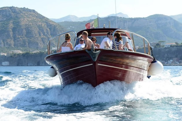 Tourists enjoy a classic wooden yacht sail off the coast of Naples.