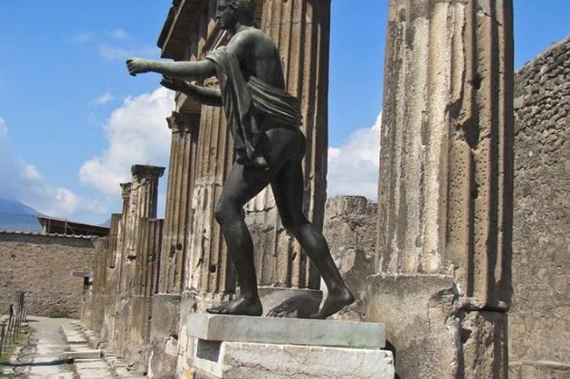 Roman statue next to columns in Pompeii.