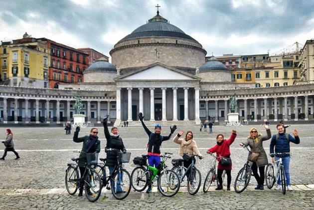 Bicyclists prepare to ride through Naples.