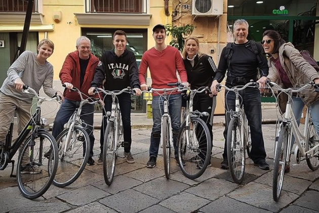 Tourists smile as they start a bike ride in Palermo.