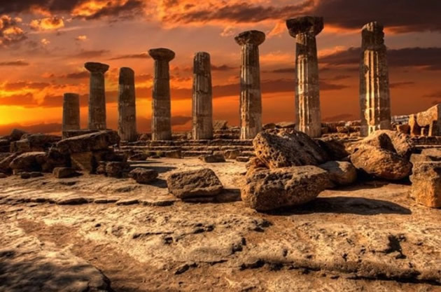 Ancient temple columns at sunset in Sicily.