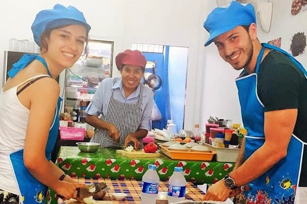 Blue-aproned students assemble ingredients in a Thai cooking class.
