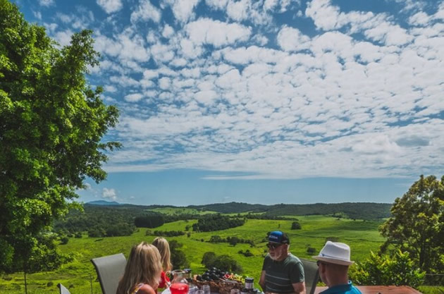 Diners enjoy an outdoor feast with views of a green valley.