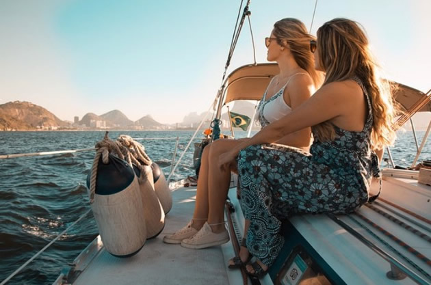 Sunglass-clad women enjoy a sailboat ride and view of blue water.