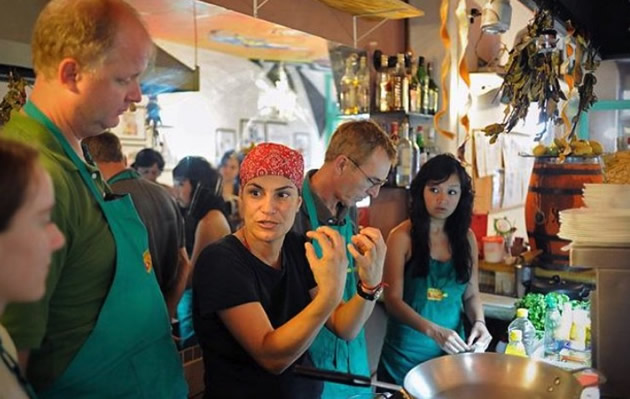 Bandana-clad local chef demonstrates a cooking technique to students.