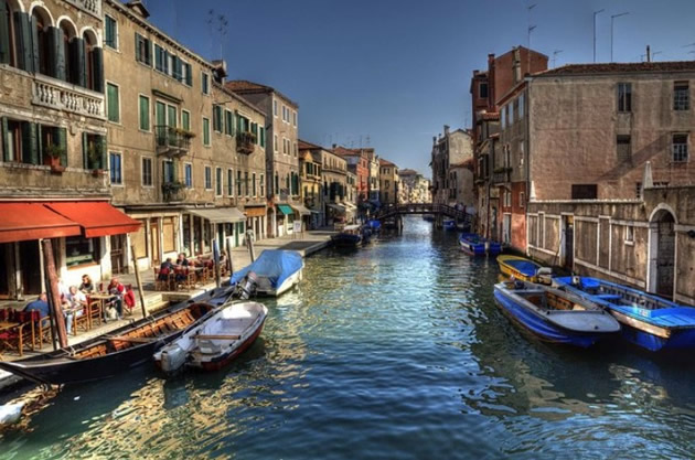 Small Venice canal with cafe diners.