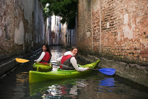 Red-jacketed tourists pose in green kayaks on a Venice canal.